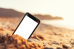 The concept of the photos on the phone. The smartphone lies buried in the sand on the beach, and takes a photo of the beach in the background. Mock up