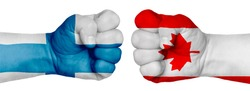 The concept of the struggle of peoples. Two hands are clenched into fists and are located opposite each other. Hands painted in the colors of the flags of the countries. Canada vs Finland