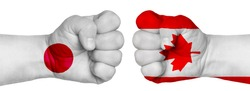 The concept of the struggle of peoples. Two hands are clenched into fists and are located opposite each other. Hands painted in the colors of the flags of the countries. Canada vs Japan