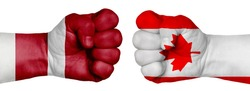The concept of the struggle of peoples. Two hands are clenched into fists and are located opposite each other. Hands painted in the colors of the flags of the countries. Canada vs Latvia