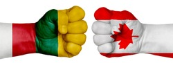 The concept of the struggle of peoples. Two hands are clenched into fists and are located opposite each other. Hands painted in the colors of the flags of the countries. Canada vs Lithuania