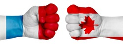 The concept of the struggle of peoples. Two hands are clenched into fists and are located opposite each other. Hands painted in the colors of the flags of the countries. Canada vs Luxembourg