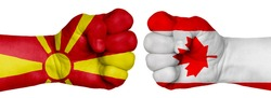 The concept of the struggle of peoples. Two hands are clenched into fists and are located opposite each other. Hands painted in the colors of the flags of the countries. Canada vs Macedonia