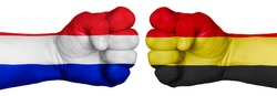 The concept of the struggle of peoples. Two hands are clenched into fists and are located opposite each other. Hands painted in the colors of the flags of the countries. France vs Belgium