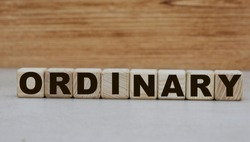 the concept of the word ordinary on cubes on a wooden background