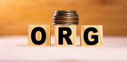 The concept of the word ORG on wooden cubes with coins on a white wooden background. Business concept.