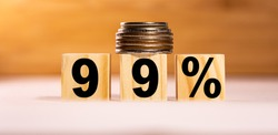 The concept of the word 99 percent on wooden cubes with coins on a white wooden background. Business concept.