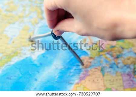 The concept of tourism and travel, vacations. Travel around the world. Planning a trip. A person measures distance on a world map using a compasses. #730529707