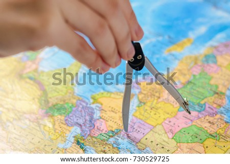 The concept of tourism and travel, vacations. Travel around the world. Planning a trip. A person measures distance on a world map using a compasses. #730529725