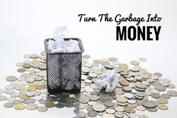 the concept of turning rubbish into money with rubbish bins surrounded by coins. Selective focus.