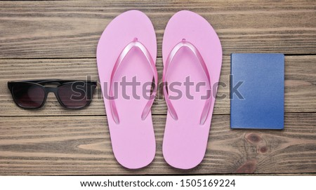 The concept of vacation on the beach, tourism. Summer traveler background. Flip flops, passport, sunglasses on wooden background. Top view. Flat lay