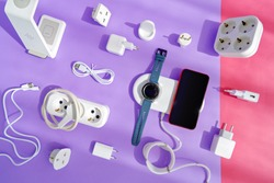 The concept of wireless charging of mobile gadgets. The smartphone and smartwatch are on the wireless charging pad. There are various adapters, cables and chargers nearby. Colored paper background.