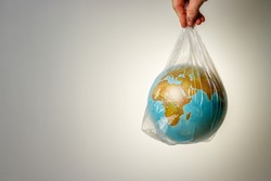 The concept of World Environment Day. The man's hand holds the earth in a plastic bag. In the blank for social advertising there is a place for the inscription.