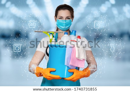 The concepts of cleaning and disinfection services.A cleaning lady in a mask stands on a blurry background with cleaning products.