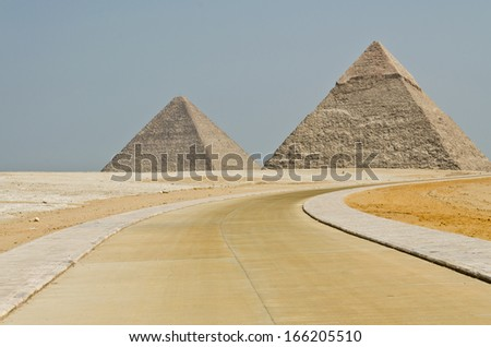 The concrete road turns to the Egyptian pyramids in the middle of barren desert under the blue sky.