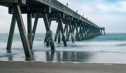 The concrete supports of Johnnie Mercer's Pier create rigid intersecting angles. The long exposure of the photograph smooths out the contours of the waves.