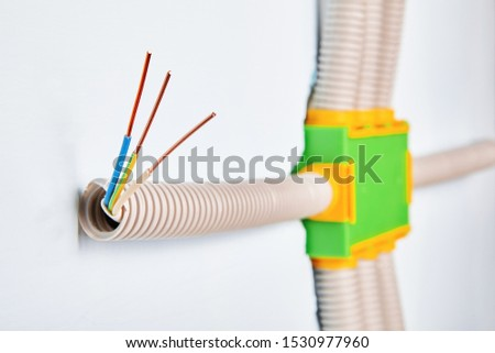 The conduit is connected to the electrical distribution box of the household wiring, the ends of the bare copper wires are visible from the outside of the pipe. Installation of a electric panel.