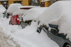 The consequences of a snowfall. Car under the snow on a city street in winter after a cyclone. Auto after snowfall. Snowstorm. Bad weather