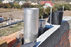 The construction of a brick chimney with two flues, steel pipes installed at different hight. Building a chimney to gas fireplace with two top vents for exhaust air out and combustion air in.