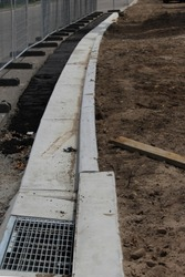 The construction of a kerb, channel and grate.