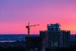 The construction site of a new residential complex against the backdrop of an incredibly beautiful sunset sky. High res and high quality image with copy space