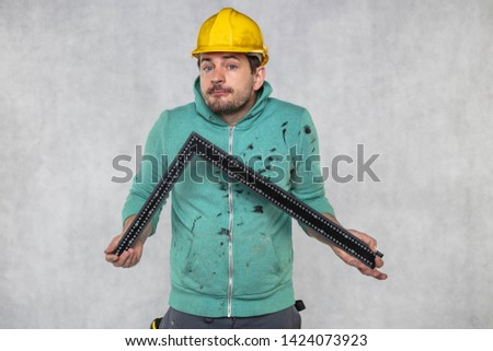 the construction worker is holding a angle in the hand, a guide to constructing right angles
