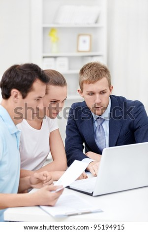 The consultant and the young couple for a laptop