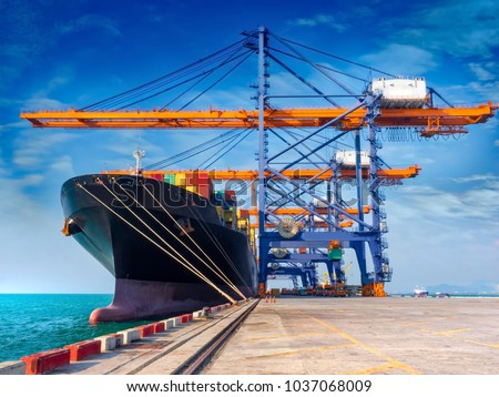The container vessel  during discharging at an industrial port and move containers to container yard by trucks. #1037068009