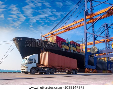 The container vessel  during discharging at an industrial port and move containers to container yard by trucks. #1038149395