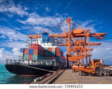 The container vessel  during discharging at an industrial port and move containers to container yard by trucks.