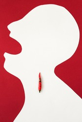 the contour of the person cut from white paper on a red background with an open mouth and hot red pepper lying inside him. cold concept, sore throat, burning in a throat, top view, flat lay.