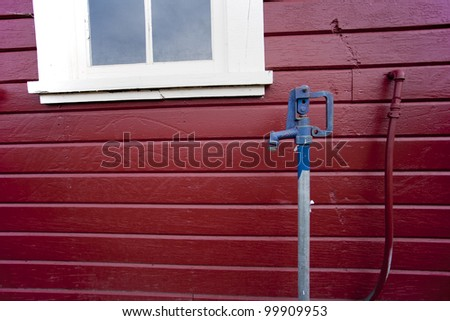 The contrast of colors of a deep red building and the blue top of a well faucet.