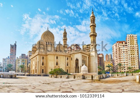 The contrast of the scenic Sidi Yaqut al-Arshi mosque, decorated with carved islamic patterns and the modern multistory living neighborhood, seen on background, Alexandria, Egypt. #1012339114