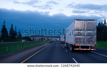 The convoy of semi trucks with reefer trailers on flat like an arrow evening road with lights on and reflection of light on a shiny trailer stainless steel doors. Trucks driving on a divided highway