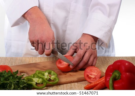The cook cuts on kitchen a board tomato rings.