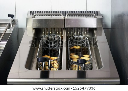 The cook fries french fries in a deep fryer. Preparation in a deep fryer. Deep fryer with boiling oil on restaurant kitchen                                #1525479836