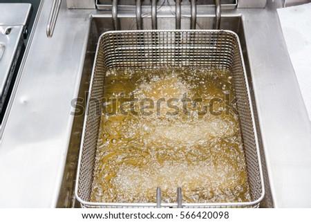 The cook fries meat in a deep fryer. Preparation in a deep fryer Stockfoto ©