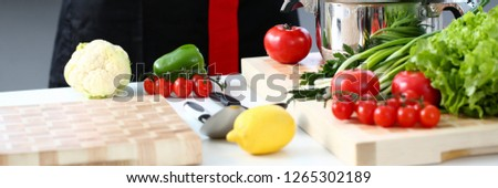 The cook in the kitchen is preparing to prepare a dish of fresh vegetables for a vegan, keeps his hands on his belt, the products lie on the table