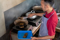 the cook lights the stove to fry the side dishes for the customers at the food stall