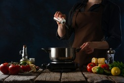 The cook prepares boiled corn with vegetables. Cooking process. On the table is a saucepan. The cook salts the water. Also in the frame are vegetables, spices. Dark background.
