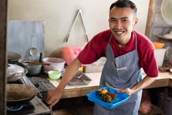 the cook smiled as he turned on the stove to fry the side dishes for the customers at the food stall