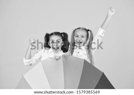 The coolest accessory in school. Happy little girls celebrating autumn holidays behind fashion accessory. Small children smiling with colorful umbrella rain accessory. Best accessory trend for fall.