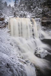 The copper colored water of Blackwater Falls in Davis, West Virginia in the Winter.