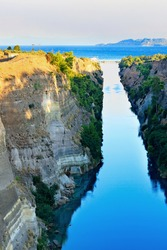 The Corinthian narrow canal in the morning haze of a summer day illuminates the bright rising sun of Greece, the canal connects the Aegean and Ionian Seas. Vertical image, copy space.