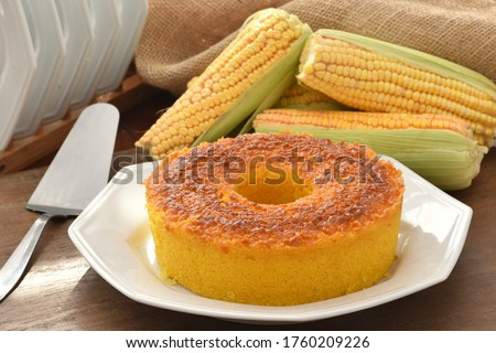 The corn cake in a plate on a wooden table with corn cobs and a wooden pot at the background
