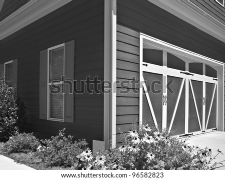 The corner of a house showing the garage doors and windows with shutters.
