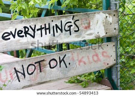 "The corner of an old walking bridge, with a boarded up section, focus on the graffiti which reads ""everything's not ok"""