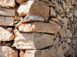 The corner of  stone wall, old stonework, texture, construction, hewn pieces of stone, ancient.