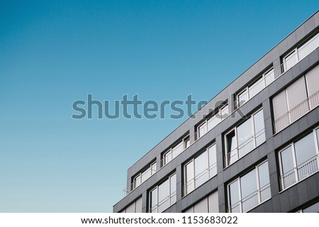The corner of the building with many windows in a minimalistic style against the blue sky. #1153683022