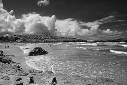 The Cornish beach at Polzeath on the North Cornwall coast, surfers and bathers enjoying the surf, sea and very dramatic white clouds in Summer time, Cornwall, UK